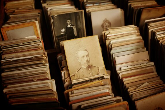 Várias fileiras de retratos antigos e amarelados graças ao tempo. Em destaque há o retrato de um homem que aparenta ter vivido entre 1870 e 1920.