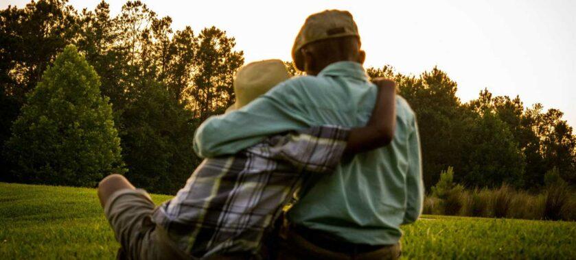 irmãos-se-abraçando-em-um-campo