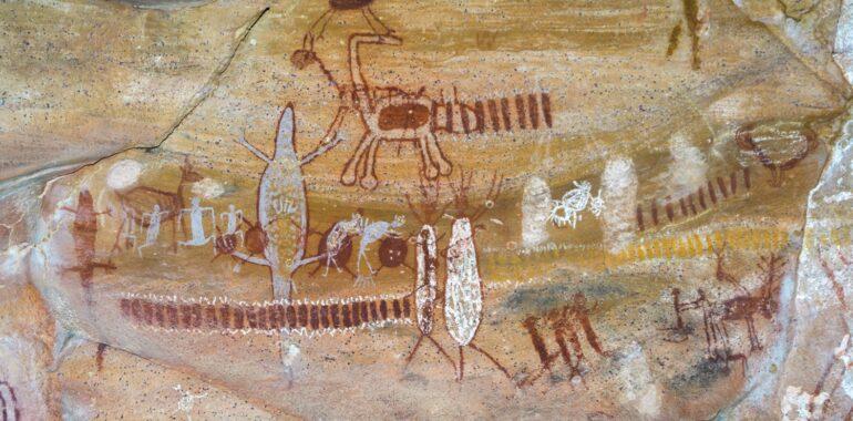 Pintura rupestre encontrada na Serra da Capivara. A pintura mostra vários animais e algumas pessoas aparentemente caçando alguns desses animais.