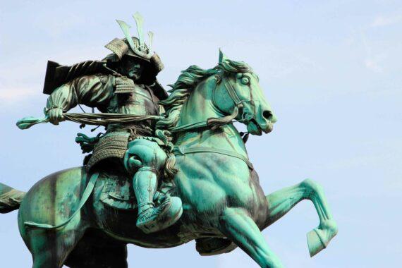 Estátua de bronze um cavaleiro samurai puxando a rédea de seu cavalo.