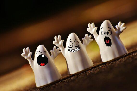 Três fantasmas de brinquedo dispostos em cima de uma mesa.