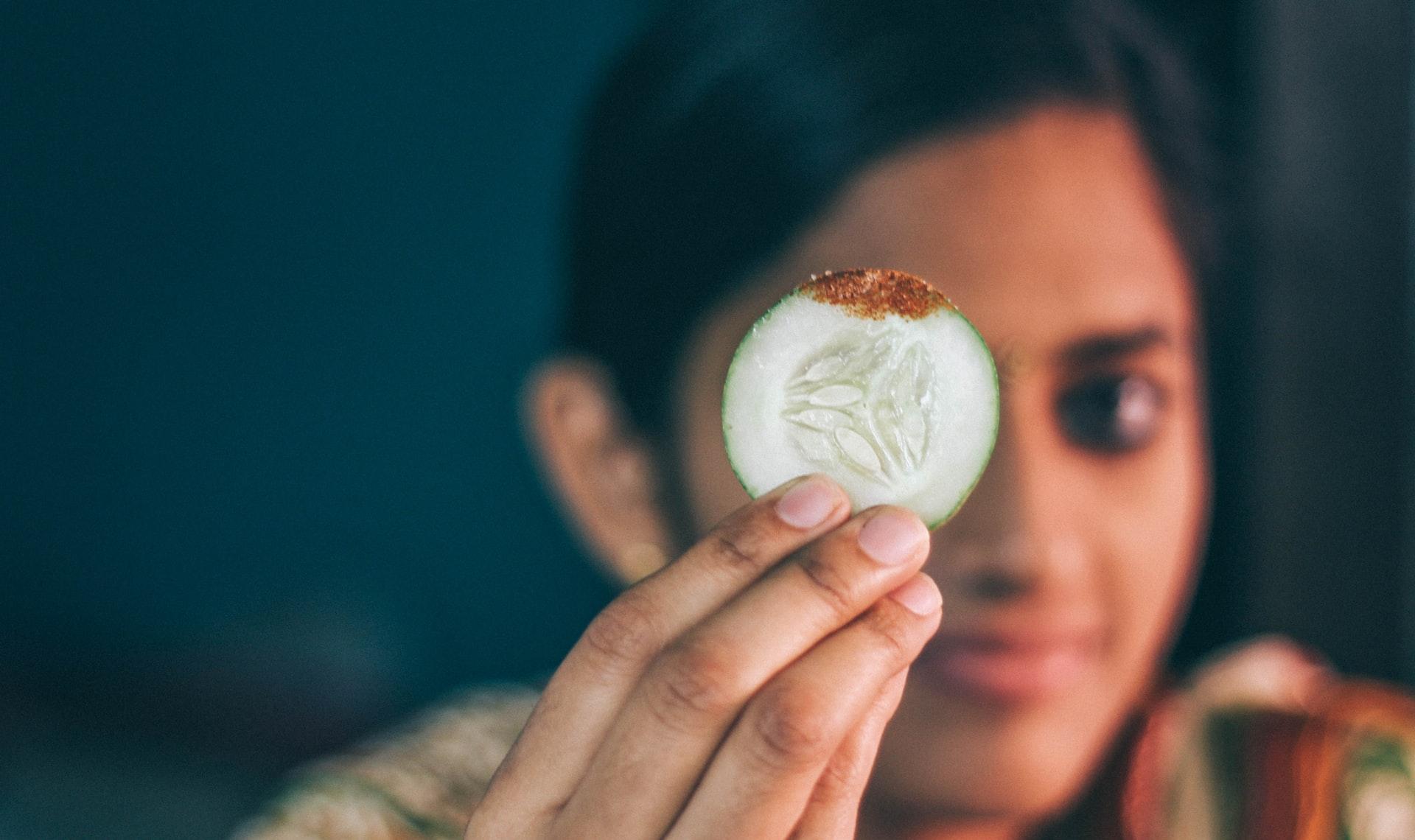 moça segurando uma fatia de pepino