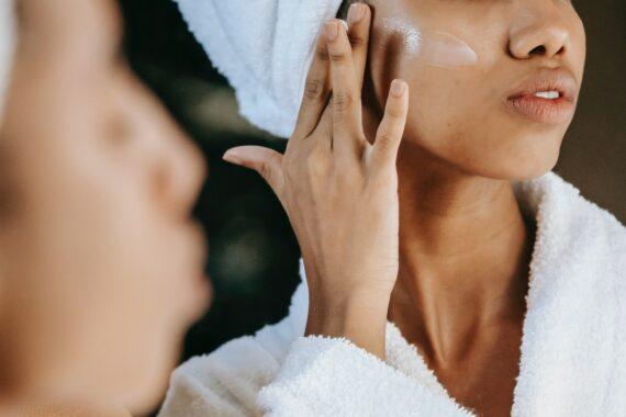 Mulher aplica produto de skincare sobre a pele.