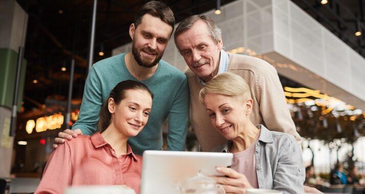 Quatro pessoas olham para a tela de um notebook